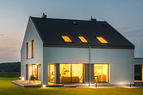 Panoramic photo of modern house with outdoor and indoor lighting, at night